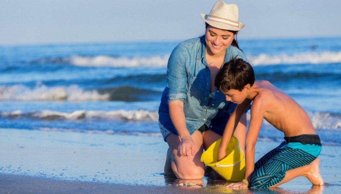 Mamma e figlio cercano conchiglie in una spiaggia ligure
