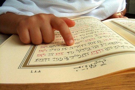 A child reading Quran pointing out the Ayah