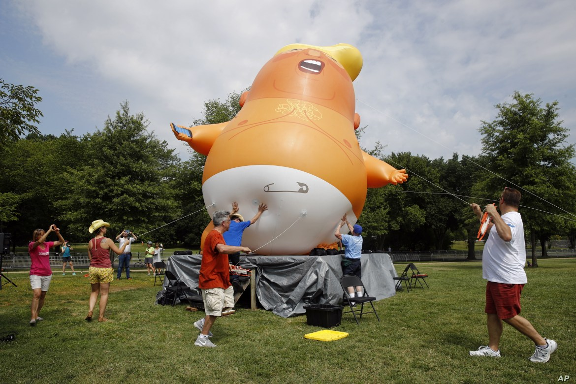 Protesters move a Baby Trump balloon into position before Independence Day celebrations, July 4, 2019, on the National Mall in Washington.
