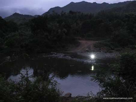 A 50K runner uses his headlamp to cross a river, just as the sun is about to rise.