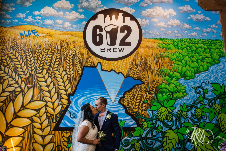 Bride and groom kissing under 612 Brew sign