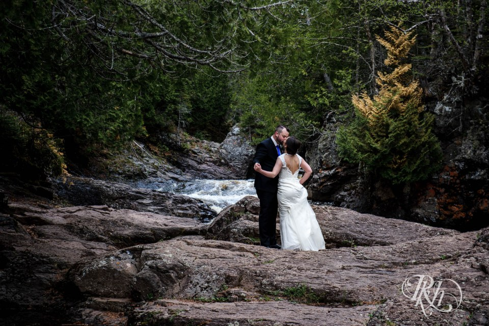 Bride and groom kissing at the bottom of a waterfall.
