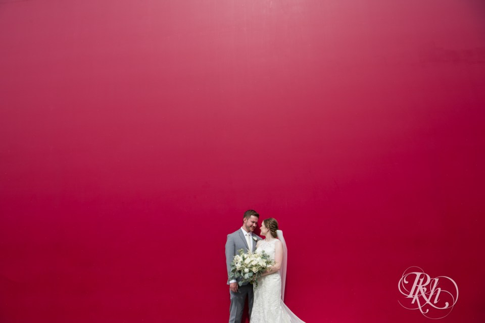 bride and groom standing in front of red wall