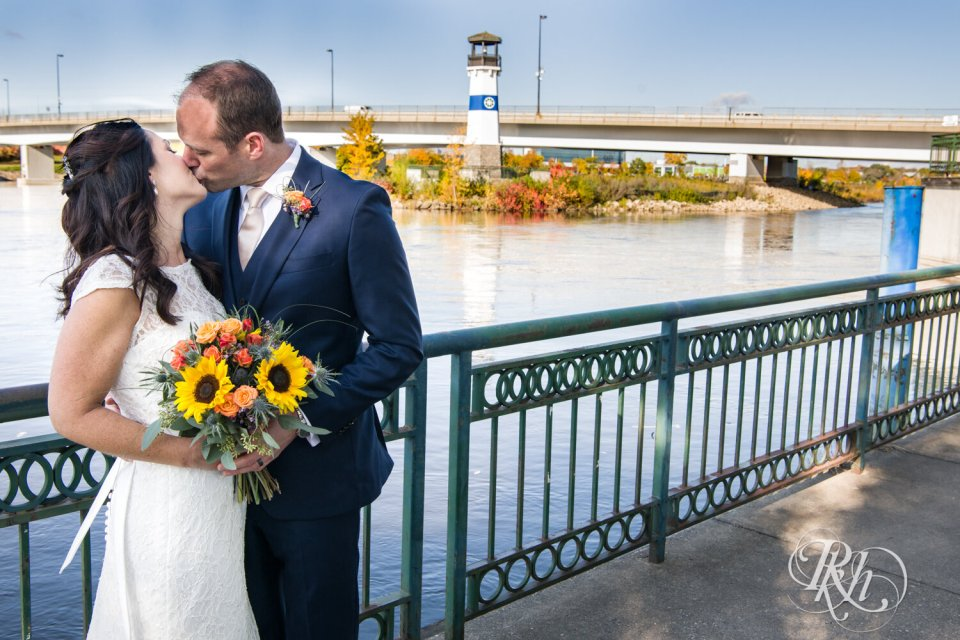 Bride and groom kiss with flowers and lighthouse