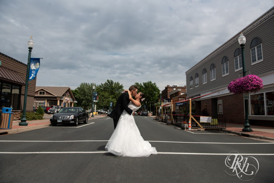 bride and groom kissing in middle of road