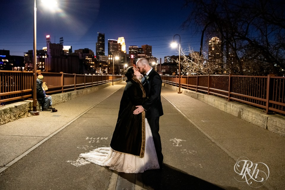 november wedding bride and groom kiss stone arch bridge night
