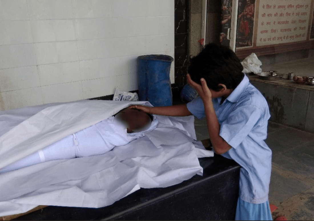 Indian boy mourning father