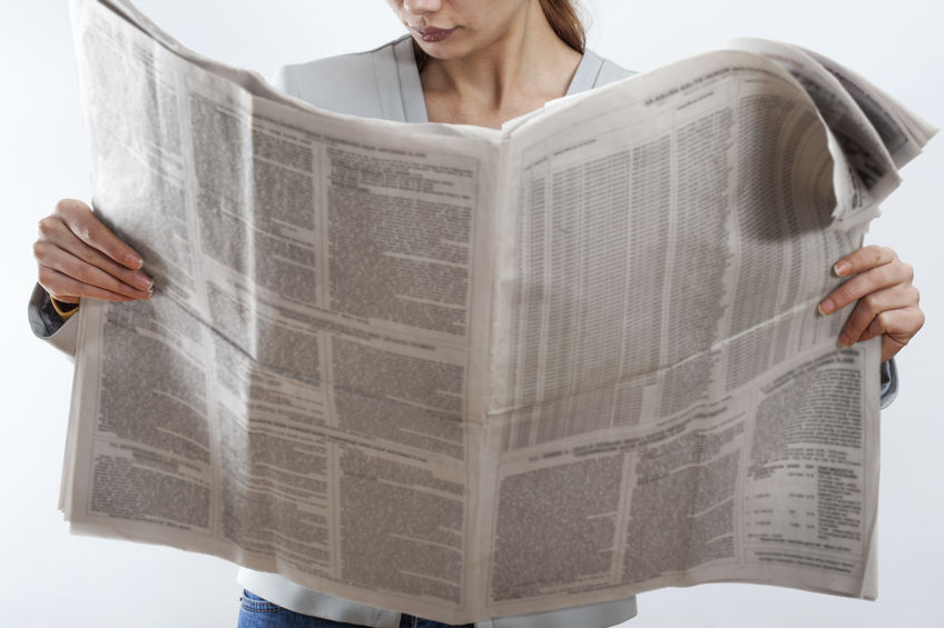 69978265 - woman reading newspaper on white background