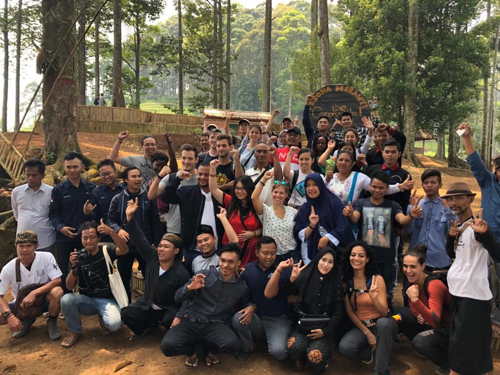 """Participants and local community members taking a group photo at the entrance of ecotourism site """"Pesona Maranti"""""""