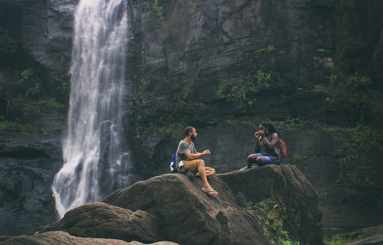 Siblings resting on a boulder in front of a waterfall