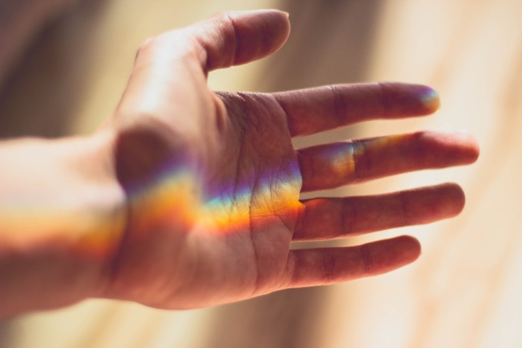 An outreached hand with a prism light shining on it