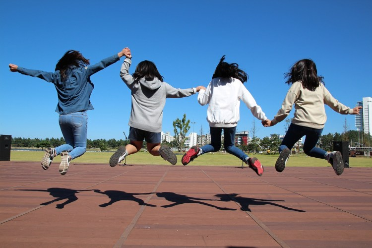 4 girls jumping on a track field