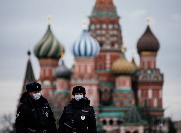"TOPSHOT - Russian police officers patrol on March 30, 2020 on the deserted Red square in front of Saint Basil's Cathedral in Moscow as the city and its surrounding regions imposed lockdowns today, that were being followed by other Russian regions in a bid to slow the spread of the COVID-19 infection caused by the novel coronavirus. - The enforcement of the strict new rules, which Moscow Mayor suddenly announced for the capital late Sunday, coincide with the beginning of a ""non-working"" week declared by Russian President the week before. (Photo by Dimitar DILKOFF / AFP) (Photo by DIMITAR DILKOFF/AFP via Getty Images)"