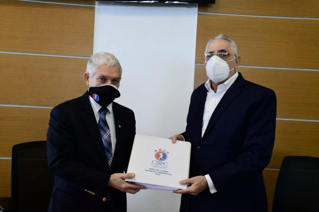 El presidente de la Liga de Béisbol Profesional de la República Dominicana, Vitelio Mejía Ortiz, recibe el documento de manos del Comisionado de Béisbol Profesional del Caribe, Juan Francisco Puello Herrera. (Foto: Fuente Externa)