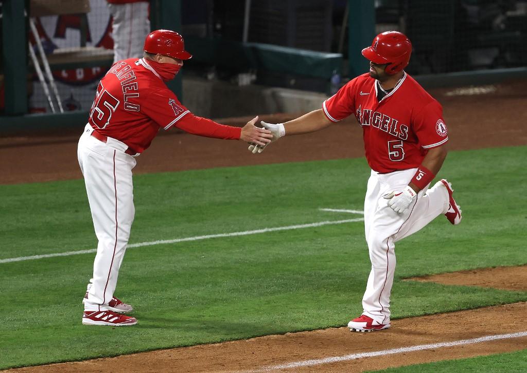Albert Pujols, #5 de Los Angeles Angels, recibe las felicitaciones del coach de tercera base, tras pegar su segundo jonrón de la temporada.  (Foto: Sean M. Haffey/Getty Images/AFP)