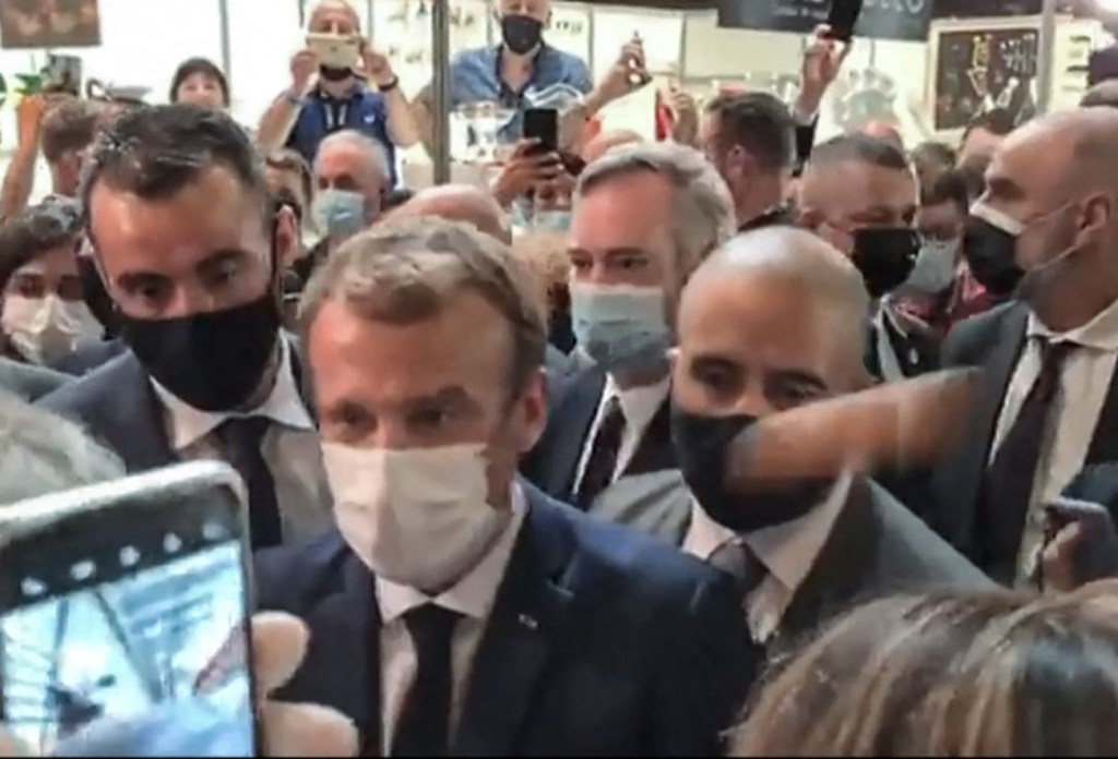This video grab made from a footage by LyonMag.com shows an egg bouncing on French President Emmanuel Macron's shoulder while he was visiting the International Catering, Hotel and Food Trade Fair (SIRHA) in the French southeastern city of Lyon on September 27, 2021. - The assailant was quickly subdued and removed from the room, with Macron saying he would try to speak with him later. (Photo by Stefano RELLANDINI / LyonMag.com / AFP) / RESTRICTED TO EDITORIAL USE - MANDATORY CREDIT AFP PHOTO / LyonMag.com