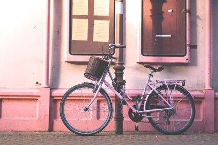 pink bike locked on a road