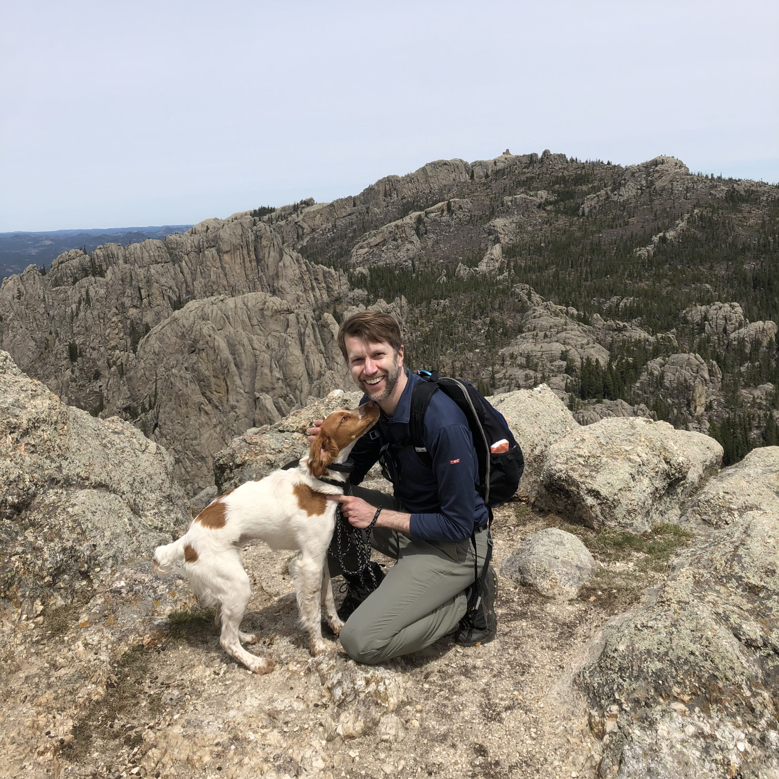 Ken petting Mae, a Brittany Spaniel dog, atop a mountain