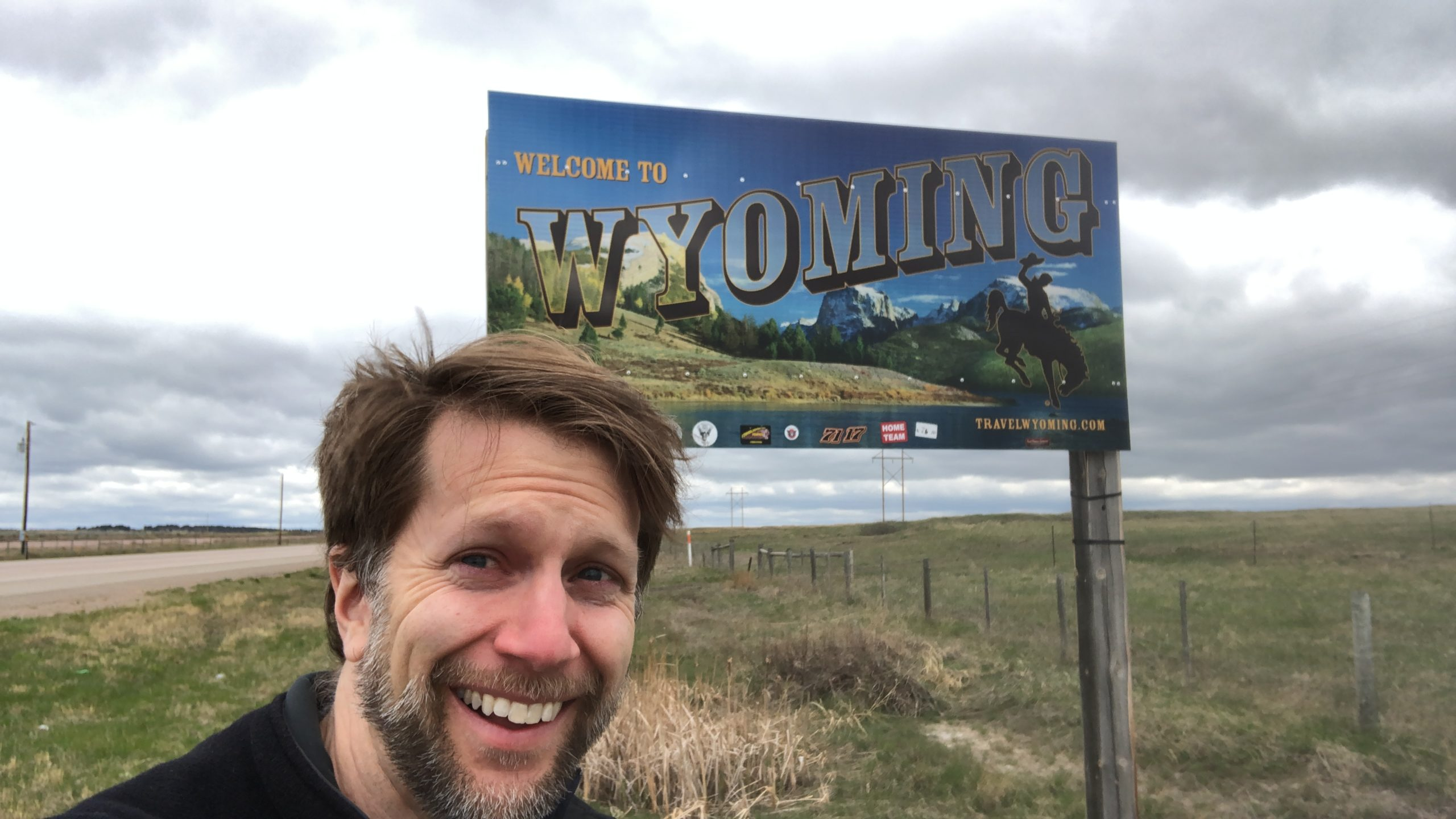 Ken in windy pose in front of Welcome to Wyoming highway sign