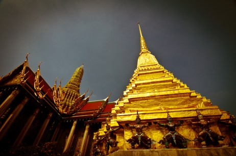 A storm hovers over the Grand Palace as the temples absorb what's left of the remaining Sun. Bangkok, Thailand.