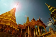 The gold leafed Thai temples twinkle in the siam sun. Bangkok, Thailand.