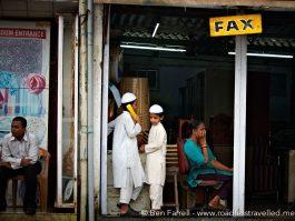 School kids use a local internet 'cafe' to make a call. Mumbai, India.