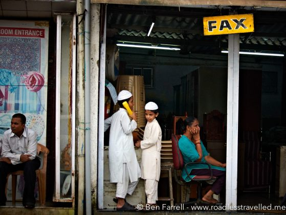 School kids use a local internet 'cafe' to make a call. Mumbai, India.