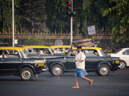 A street vendor runs through the chaotic traffic outside central station in Mumbai, India.