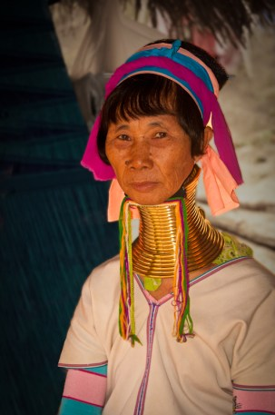 A tribal woman poses for a photo in an ancient hill-tribe. Chiang Mai, Thailand.