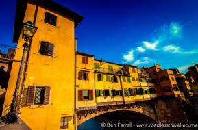 The Ponte Vecchio - the only original bridge to survive the world war bombings, reflects the afternoon sunset. Florence, Italy.