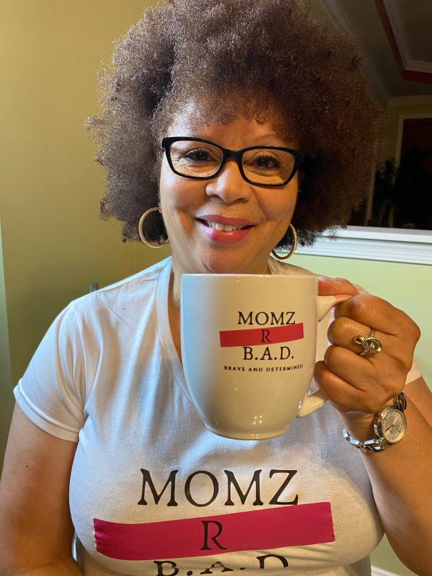 Model holding Momz R B.A.D. (Brave And Determined) Coffee Mug in pink, black and white