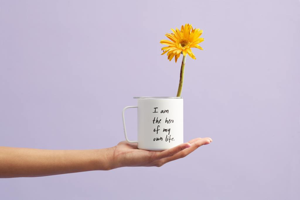 Quoted cup with sunflower in it