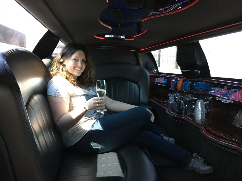 Inside stretch limo with glass of champagne