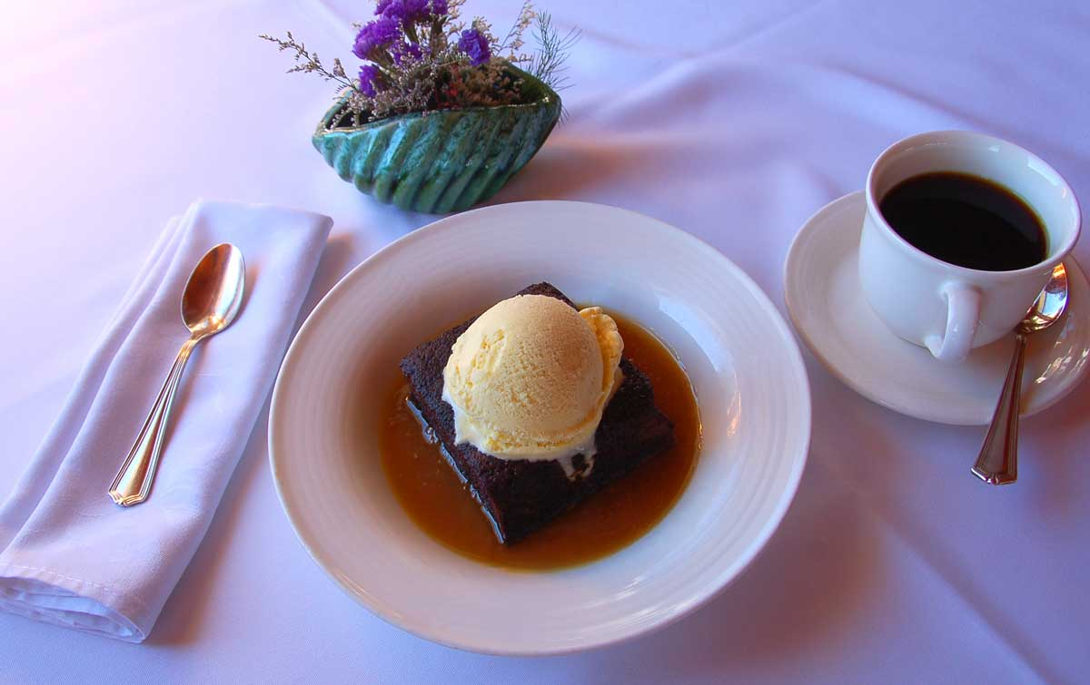 Sticky Date Pudding in a dish with black coffee