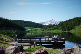 Deep blue lake with green mountain sides and a bridge into the water for fishing