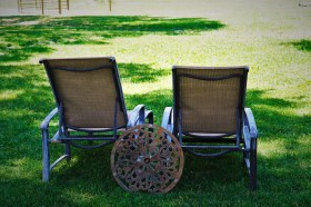 backs of 2 chairs in grass