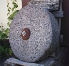 grey grist stone on wooden chair
