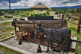 Iron statue of a burro by mining cart in mountain town