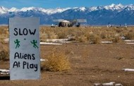 aliens at play sign near watchtower with mountains in background