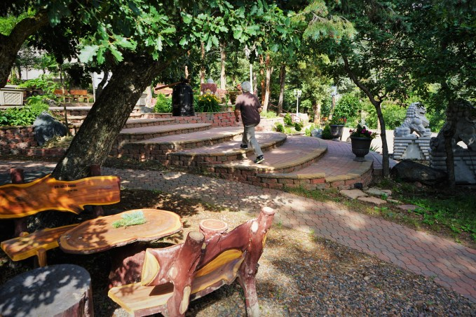 wooden benches and a rounded stone staircase in the trees
