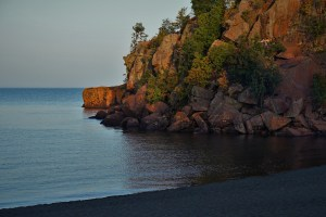 Sunset at a black sand beach with rock wall