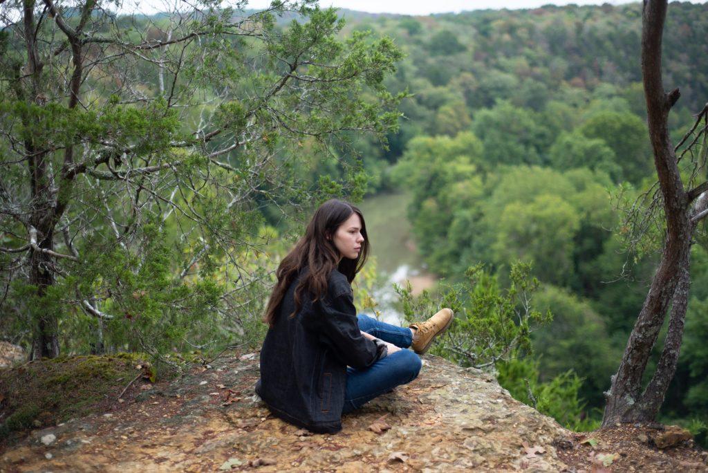 Nainen istuu Montgomery Bell State Parkin näköalapaikalla joen yläpuolella.