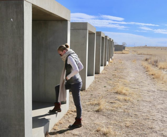 Exploring a collection of concrete sculptures by Donald Judd outside the Chinati Foundation.