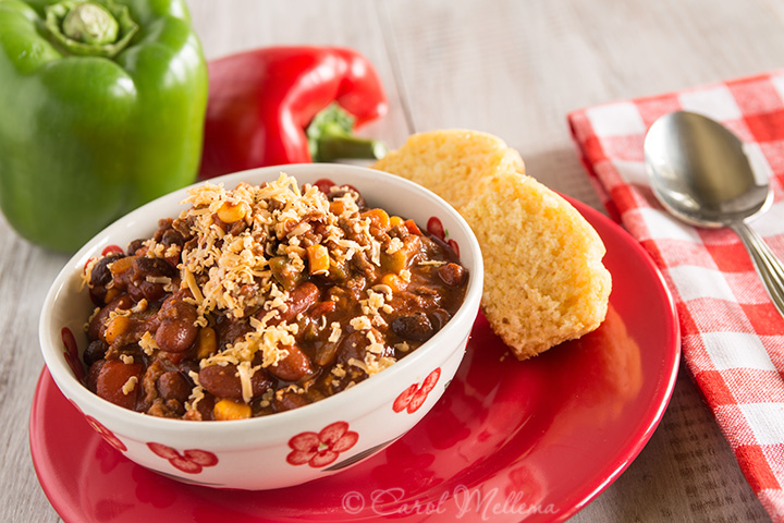 Bowl of warm chili winter comfort food dinner with corn bread muffin and red and green pepper
