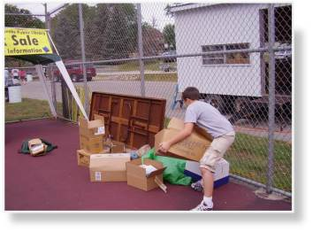 A photo of stacking the unloaded boxes of books on the tennis court in the Library booth's designated area.