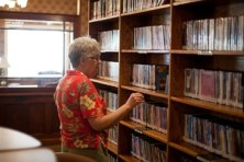 Photograph shows a patron browsing the library's shelves