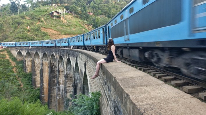 Complete guide to Sri Lanka 2019: Jenny is sitting on the edge of the nine arches bridge in Ella. A train comes whizzing through before she  can move from her seat making a lovely photo.