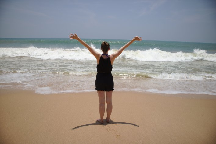 Complete guide to Sri Lanka 2019: Jenny standing on the beach admiring the waves, warm sand and cool sea.