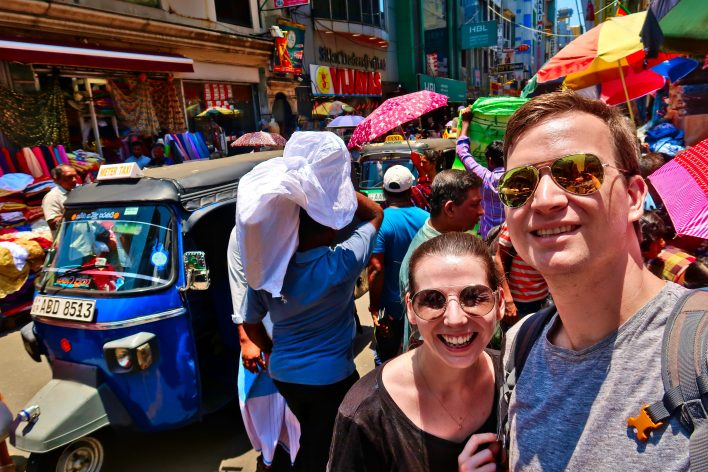Complete guide to Sri Lanka 2019: Rob and Jenny standing in front of the market vendors, porters and tuk-tuks of Pettah market