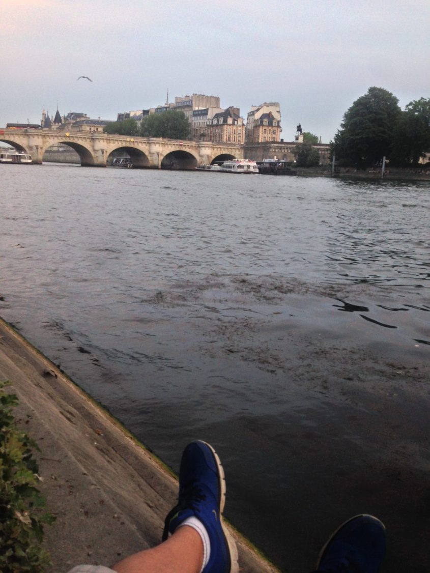 traveling alone and sitting on the banks of the Seine River in Paris